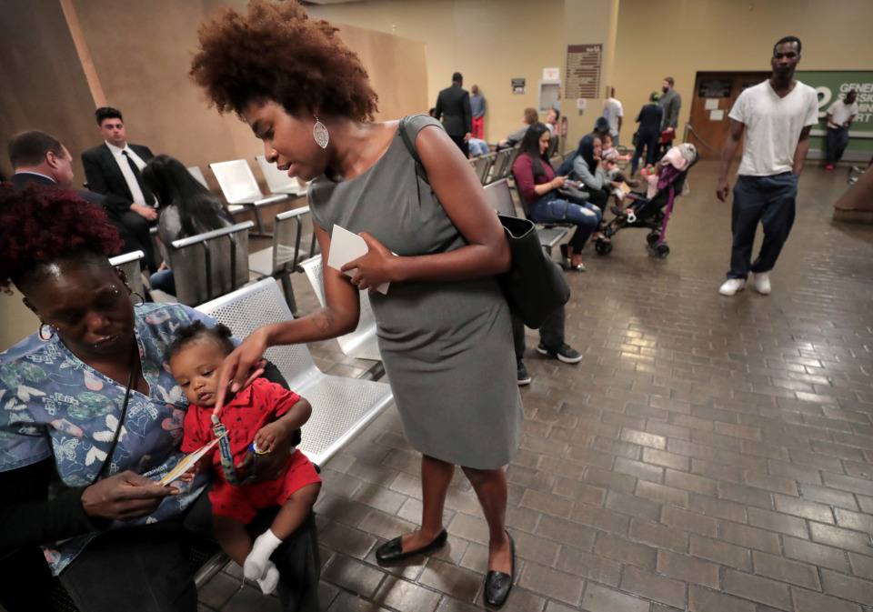 <strong>Erica Perry, a lawyer with the Memphis branch of Black Lives Matter, passes out what amounts to a get-out-of-jail card as she canvasses General Sessions Court on Wednesday, May 8, looking for mothers in need of bail money. The local advocacy group is looking to bail several low-income mothers out of jail in time for them to enjoy Mother's Day with their children.</strong> (Jim Weber/Daily Memphian)