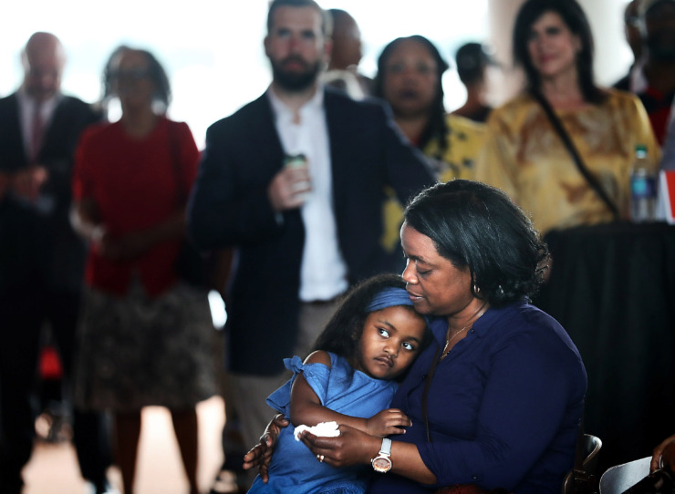 <strong>Charmeal Alexander, a descendant of Tom Lee, listens to speeches with her daughter Aria, 5, during a gathering at Beale Street Landing to honor the Memphis hero who rescued 32 people from the Mississippi River 94 years ago.</strong> (Jim Weber/Daily Memphian)