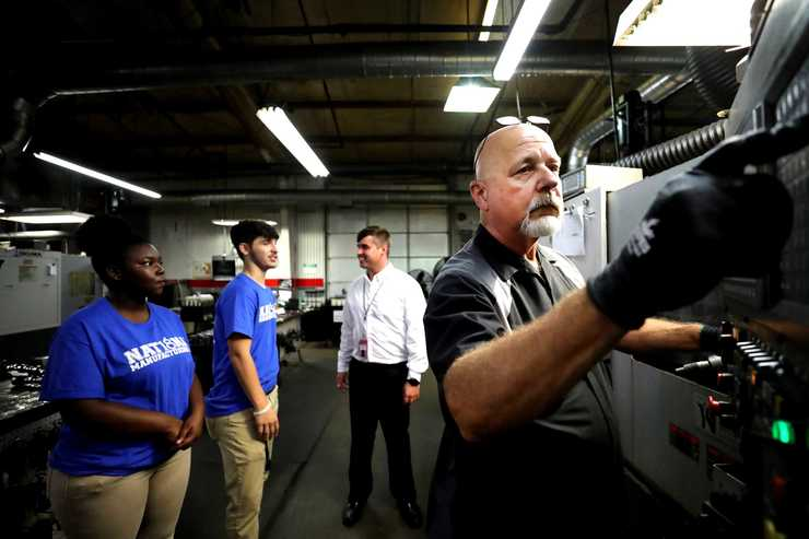 <strong>Kenny Arendale, right, one of Competition Cams' original employees, shows students from Bolton High School how to operate a piece of the company's machinery. </strong>(Houston Cofield/Daily Memphian)