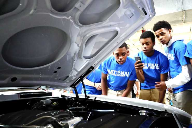 <strong>Bolton High School students study a Ford Mustang engine that Competition Cams helped build.  </strong>(Houston Cofield/Daily Memphian)