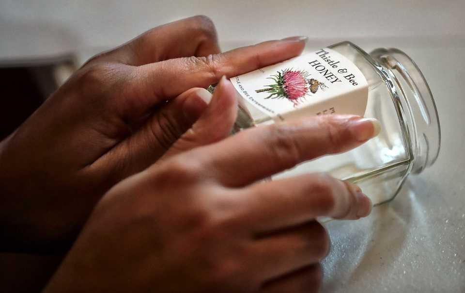 <strong>Labels are affixed to jars during the honey harvest by Thistle &amp; Bee clients and volunteers at St. Columba Episcopal Conference Center in Bartlett.&nbsp;</strong>(Jim Weber/Daily Memphian)