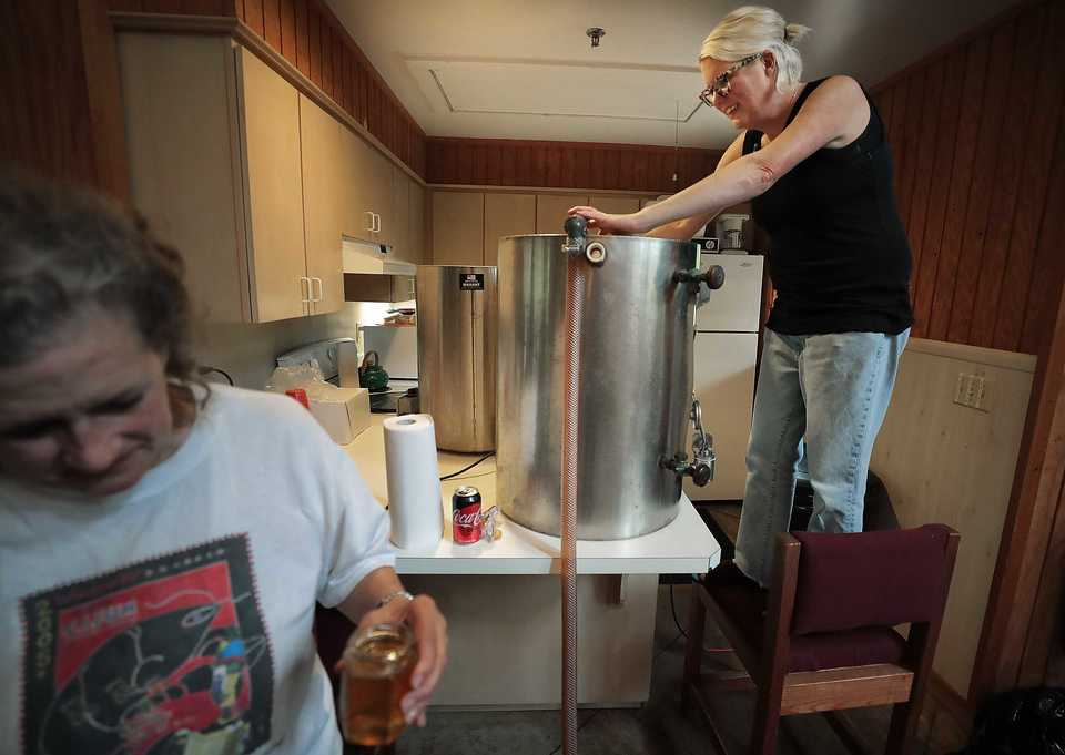 <strong>Thistle &amp; Bee volunteer Madge Deacon (left) and Executive Director Jordan Boss work to filter the honey under production at St. Columba Episcopal Conference Center in Bartlett.</strong> (Jim Weber/Daily Memphian)