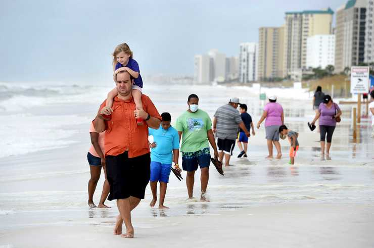 <strong>Nick Severson carries his daughter, Aubrey, on his shoulders as they and other curious onlookers walk the beach in Destin, Fla., on Tuesday, Oct. 9, as waves from Hurricane Michael pound the shoreline of this Florida panhandle resort town.</strong> (Devon Ravine/Associated Press)