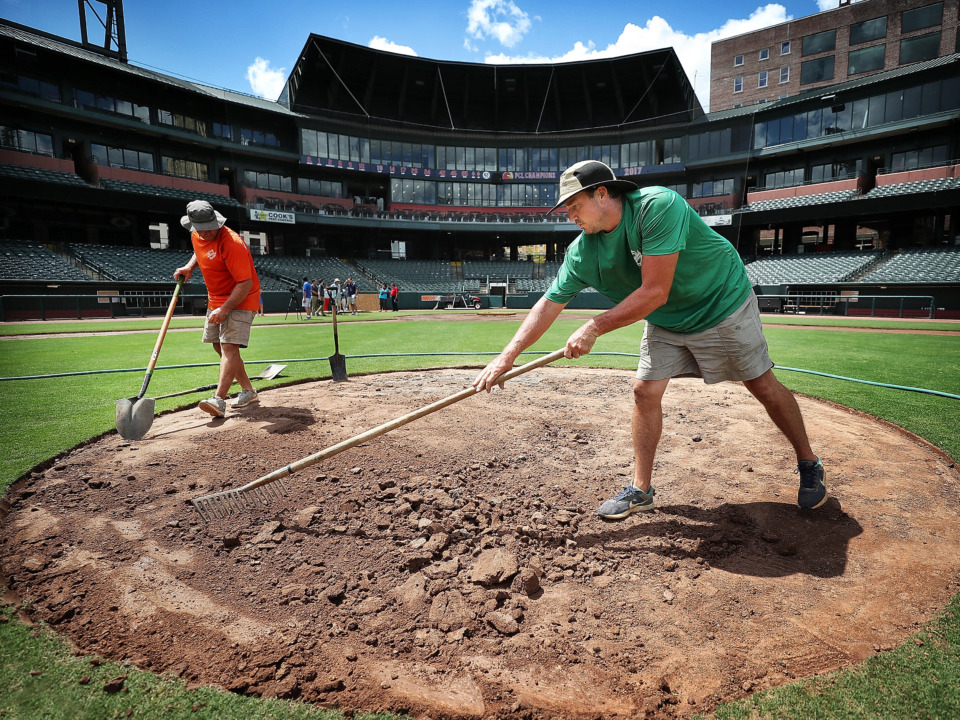 <strong>Charles Brunettie (left) and Geoffrey King smooth out the pitchers mound at Autozone Park on August 28, 2018, making field changes necessary to convert a baseball field into a soccer pitch.</strong> (Daily Memphian file)