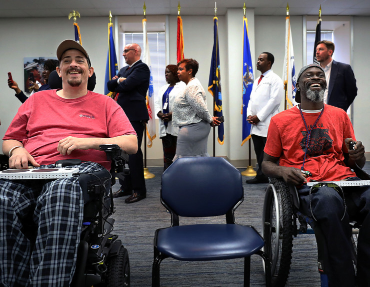 <strong>Navy veterans Michael Smith (left) and Anthony Gilliam enjoy a round of video games while members of the media interview Department of Veterans Affairs Secretary Robert Wilkie on Thursday, May 16.</strong> <strong>&ldquo;Instead of sitting at home and watching TV all day, now they can actually game,&rdquo; Gilliam said. &ldquo;This opens the door to gamers of different disabilities.&rdquo;</strong> (Patrick Lantrip/Daily Memphian)