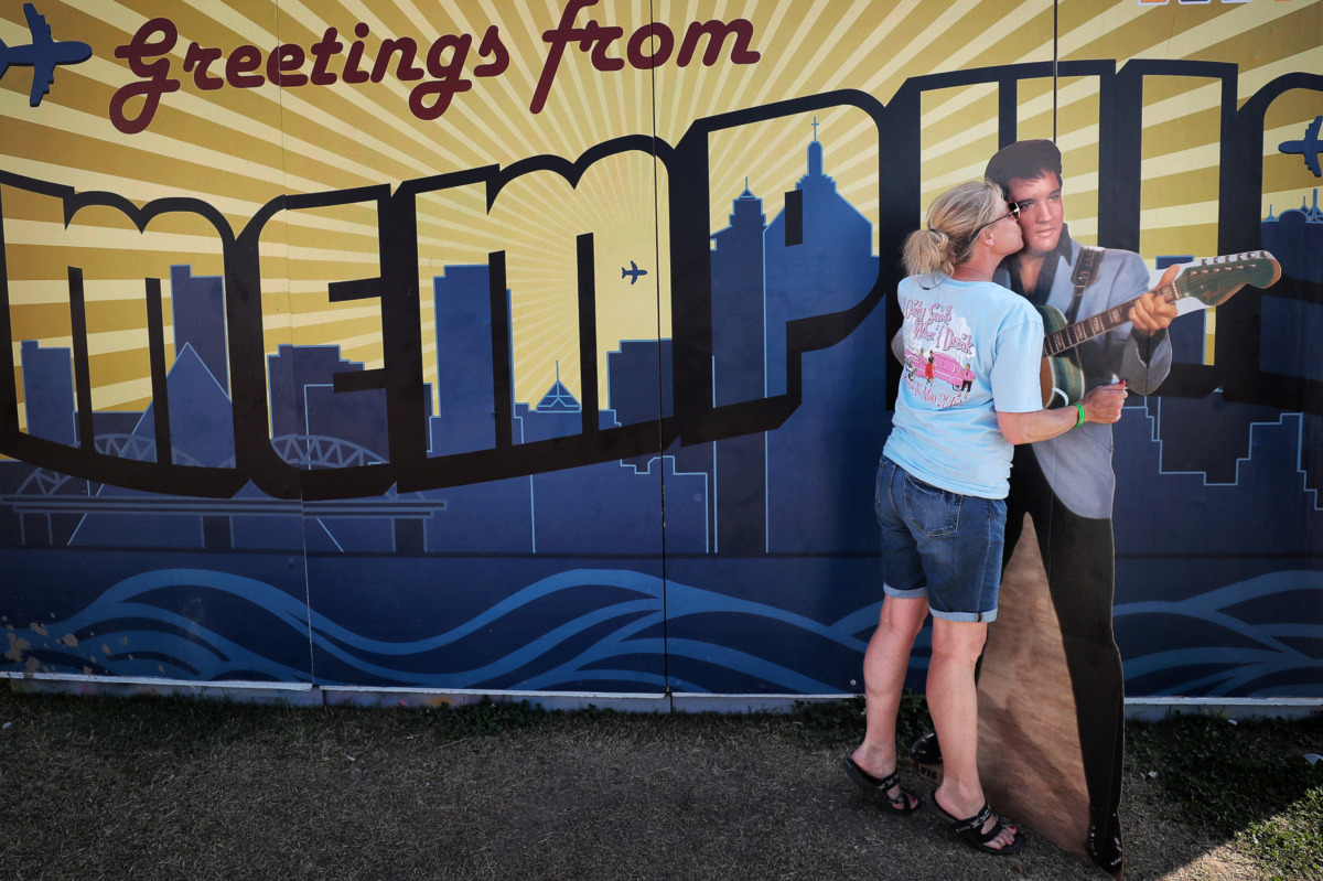 """<strong>Cheryl Benson with the """"I Only Smoke When I Drink"""" team gives Elvis a little affection on the final day of the 2019 Memphis in May World Championship Barbecue Cooking Contest at Tom Lee Park on May, 18, 2019.</strong> (Jim Weber/Daily Memphian)"""