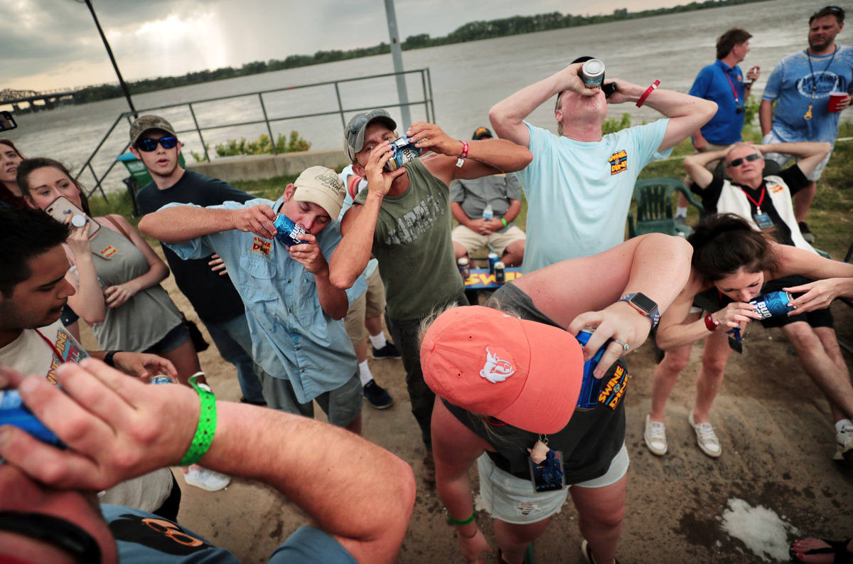 <strong>The Swine &amp; Dine team unwinds with a beer shotgun showdown on the final day of the 2019 Memphis in May World Championship Barbecue Cooking Contest at Tom Lee Park on May, 18, 2019.</strong> (Jim Weber/Daily Memphian)