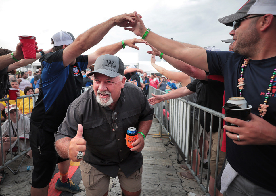 "<strong>Dan Judd with Southern Smokers leads his team to the stage after winning the ""Patio Porkers"" division during the awards ceremony on the final day of the 2019 Memphis in May World Championship Barbecue Cooking Contest at Tom Lee Park on May, 18, 2019.</strong> (Jim Weber/Daily Memphian)"