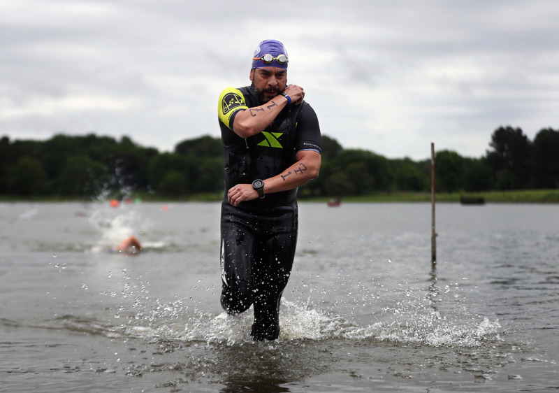<strong>Francisco Alatorre works to quickly remove his wetsuit as he emerges from the water en route to the bicycle portion of the Memphis in May Olympic Triathlon on Sunday, May 19.</strong> (Patrick Lantrip/Daily Memphian)