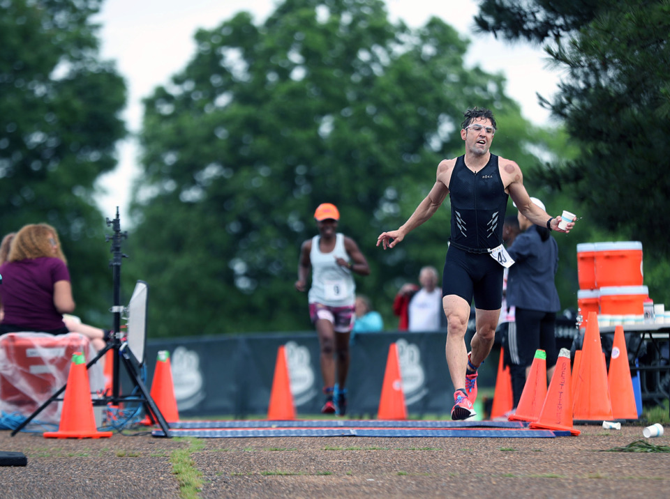 <strong>Anthony McManus snags a much-needed cup of water as he makes his way along the final stretch of the Memphis in May Olympic Triathlon on Sunday, May 19.</strong> (Patrick Lantrip/Daily Memphian)