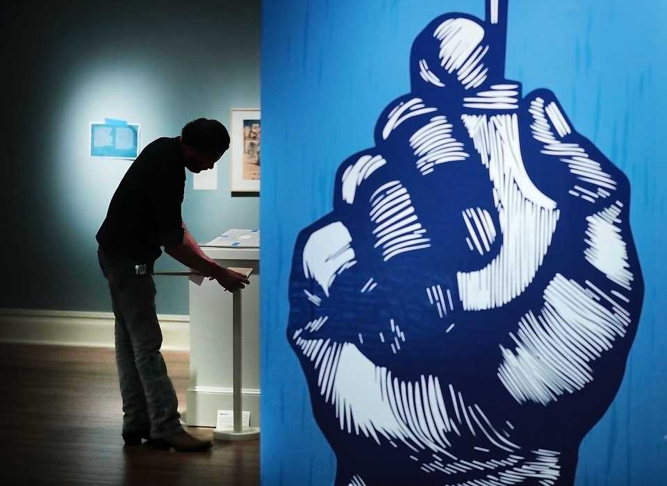 "<strong>Dixon Gallery and Gardens preparator Jeff Goggans finishes the installation of the exhibition ""El Taller de Gráfica Popular: Vida y"" on Wednesday, Oct. 10. The exhibit, which translates to ""The People's Print Workshop: Life and Art,"" displays work from a Mexican printmaking workshop founded in 1937 with a mission of social and political printmaking.</strong> (Jim Weber/Daily Memphian)"