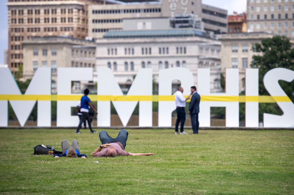 <strong>Artist Tylur French lies on the grass with his son Lincoln French ahead of the official unveiling of a new Memphis sculpture made by French and his art production team Youngblood Studio on May 22, 2019, in Mud Island River Park.</strong> (Brandon Dill/Special To The Daily Memphian)