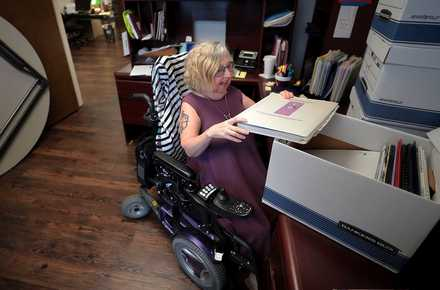 <strong>Sandi Klink, executive director of the Memphis Center for Independent Living, unpacks boxes as the local nonprofit settles into its new office space in Clark Tower in East Memphis.</strong> (Jim Weber/Daily Memphian)