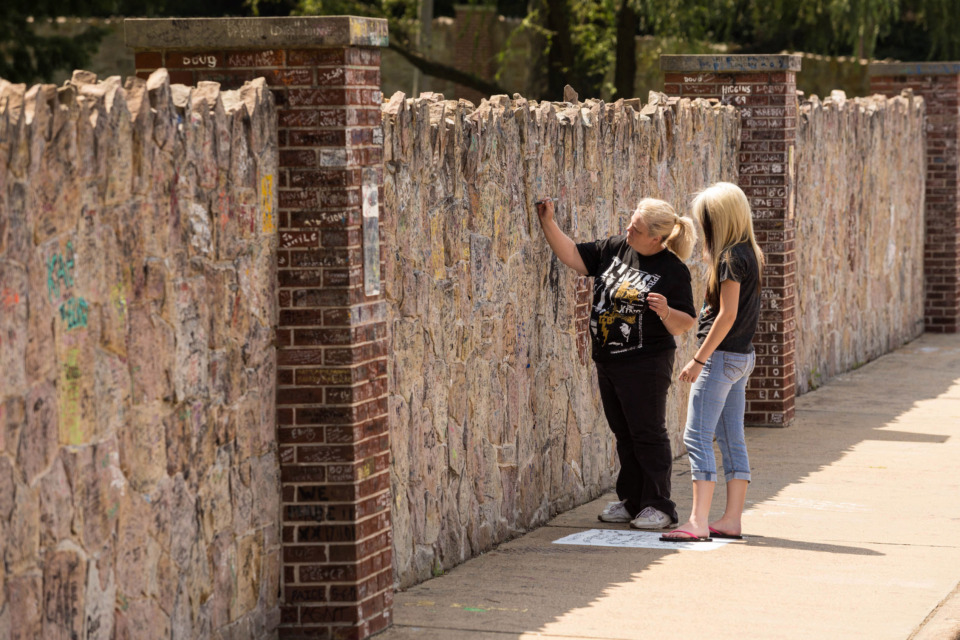 "<strong>Elvis fans sign the wall in front of Graceland during Elvis week. Graceland managing partner Joel Weinshanker says the city and the Memphis Grizzlies front office are blocking the <span class=""PrepopulatedMention__mention___2XlYb"" spellcheck=""false"">Graceland</span> development deal over 80,000 square feet of new soundstages.&nbsp;</strong>(Daily Memphian file)"