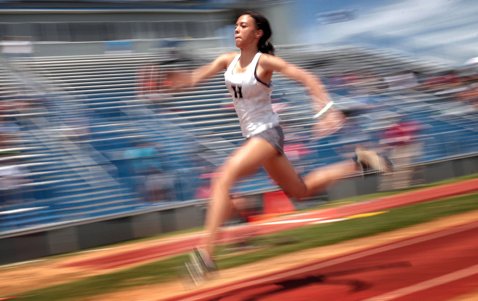 <strong>In this slow shutter speed photo, Houston's Kyla McLaurin flashes by the bleachers while competing in the AAA girl's triple-jump during the Spring Fling Class AAA state track finals at MTSU in Murfreesboro on May 23, 2019.</strong> (Jim Weber/Daily Memphian)