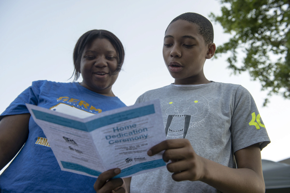 <strong>Charniqua Johnson (left), 17, and Tylan Thompson, 12, participate in a Habitat for Humanity home dedication ceremony in the Bearwater Park neighborhood for new homeowners, including their family, throughout the city on May 23, 2019.</strong> (Brandon Dill/Special To The Daily Memphian)