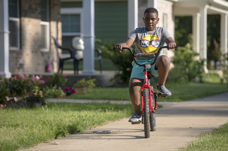 <strong>Kaleb Boswell, 8, rides his bike during a Habitat for Humanity home dedication ceremony in the Bearwater Park neighborhood for new homeowners, including Boswell's family, on May 23, 2019. The new homes are located throughout Memphis.&nbsp;</strong>(Brandon Dill/Special To The Daily Memphian)