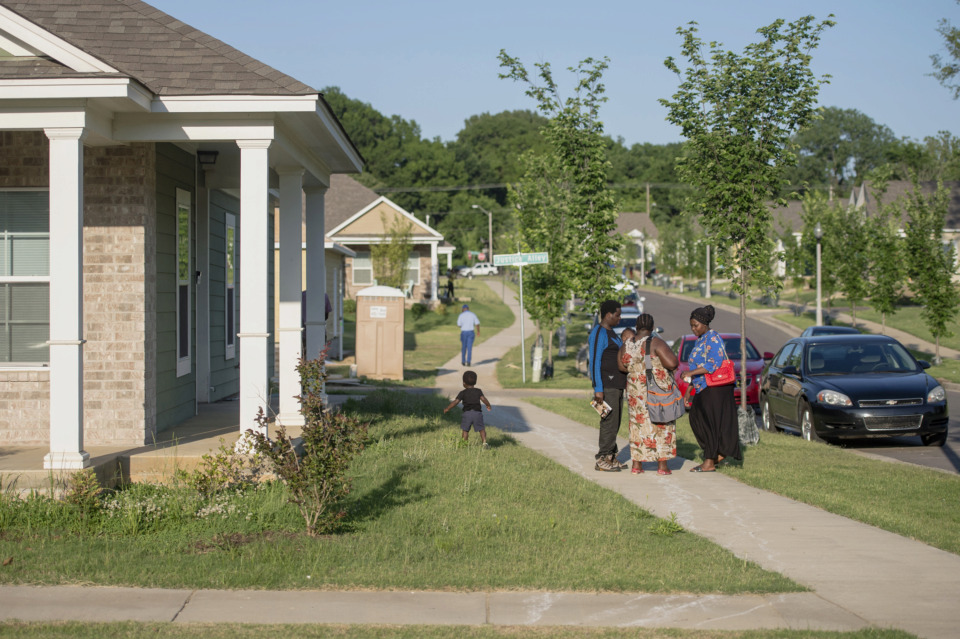<strong>Residents walk outside after a Habitat for Humanity home dedication ceremony in the Bearwater Park neighborhood for nine new homeowners throughout the city on May 23, 2019. Each family was presented with a ceremonial key to their house.</strong> (Brandon Dill/Special To The Daily Memphian)