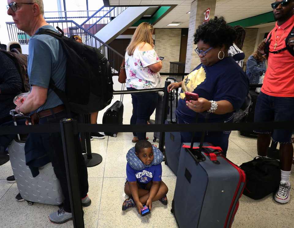 <strong>Kingman Johnson waits in line with his mother, Christine Neal (right), to check their bags for a flight from Memphis International Airport to Fort Lauderdale, Florida, on Friday, May 24. Passenger activity at Memphis International is increasing by nearly 5% a year.</strong> (Patrick Lantrip/Daily Memphian)