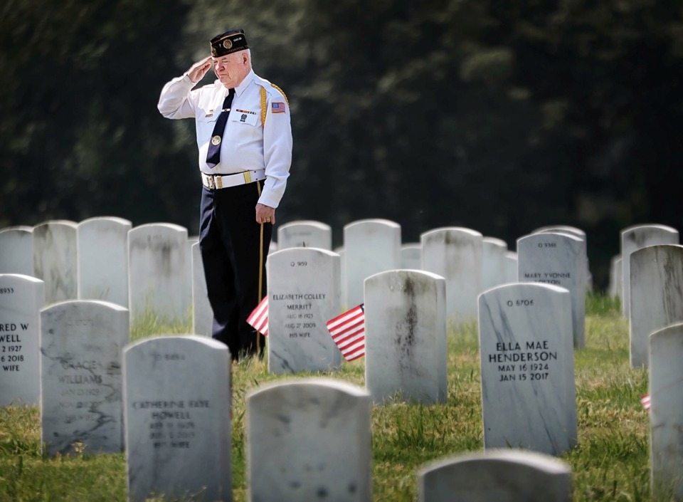 <strong>Vietnam veteran Ron Roberson salutes his parents' grave marker, both of whom served in the military, before the start of the annual Memorial Day ceremony at the West Tennessee State Veterans Cemetery on Monday, May 27.</strong> (Jim Weber/Daily Memphian)