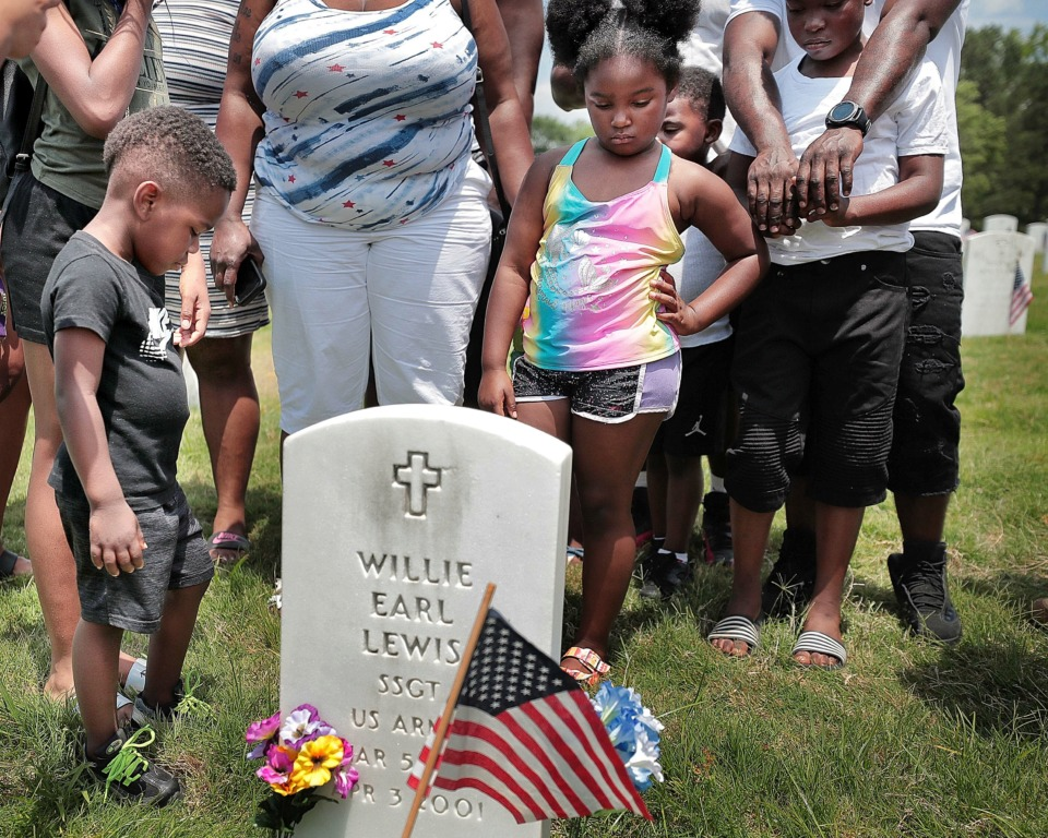 <strong>Family members gather around the grave of U.S. Army Sgt. Willie Earl Lewis to pay their respects after the annual Memorial Day ceremony at the West Tennessee State Veterans Cemetery on Monday, May 27.</strong> (Jim Weber/Daily Memphian)