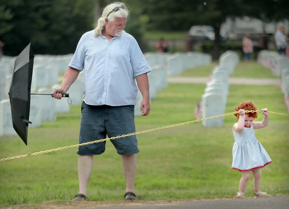 <strong>Keegan Wagner, 3, tries to find her own way out of the cemetery as she walks with her grandfather Lonny Daugherty after the annual Memorial Day ceremony at the West Tennessee State Veterans Cemetery on Monday, May 27.</strong> (Jim Weber/Daily Memphian)