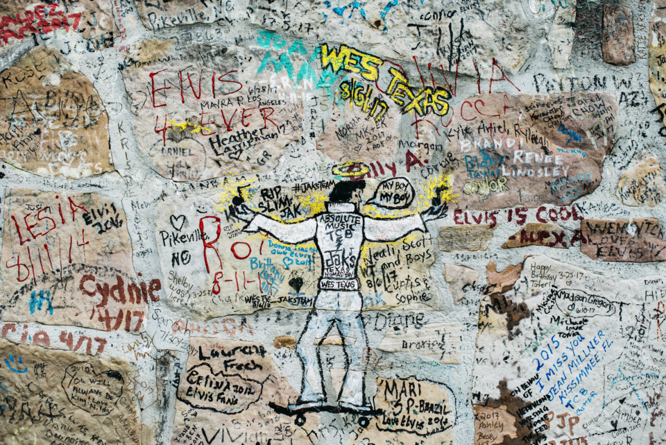 <strong>Graceland visitors pay tribute to Elvis Presley on the wall surrounding the late singer's mansion. Elvis Presley Enterprises is at odds with city government and the Memphis Grizzlies over a deal to expand the Graceland campus.</strong> (Jim Weber/Daily Memphian file)