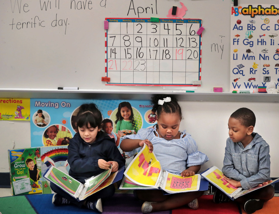 <strong>Students Danna Galvan (left), Eryn Wilbern and Jameson Dugger read together in Alice Holman's prekindergarten class at Porter-Leath's Douglas Head Start School on April 23. Shelby County commissioners are deciding whether to provide an additional $2.5 million to help replace an $8 million federal grant that funds 1,000 countywide prekindergarten seats.</strong> (Jim Weber/Daily Memphian file)