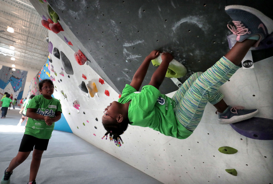 <strong>Auria Bell, 7, goes topsy-turvy while trying to climb one of the freestyle walls during a session of Camp Day2Day, a free diabetes camp for kids ages 7-16, at the Memphis Rox gym on June 4, 2019. The camp helps kids learn how to manage their diabetes through nutrition and exercise.</strong> (Jim Weber/Daily Memphian)