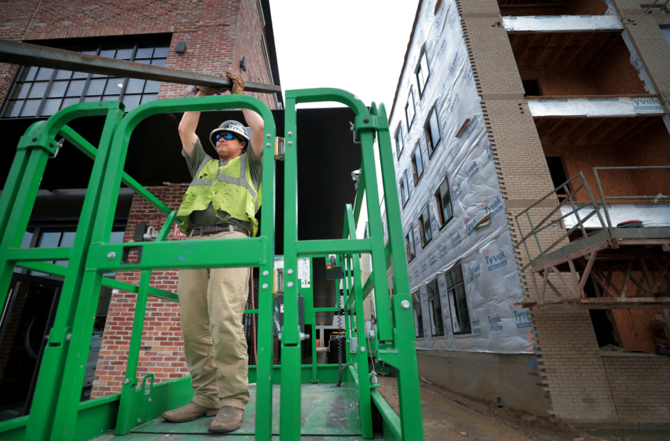 <strong>Michael Durham works on improvements to the facade of the former Wonder Bread factory as construction continues next door on The Rise apartment complex on Monroe, part of the rapid revitalization efforts in the Edge District.</strong> (Jim Weber/Daily Memphian)