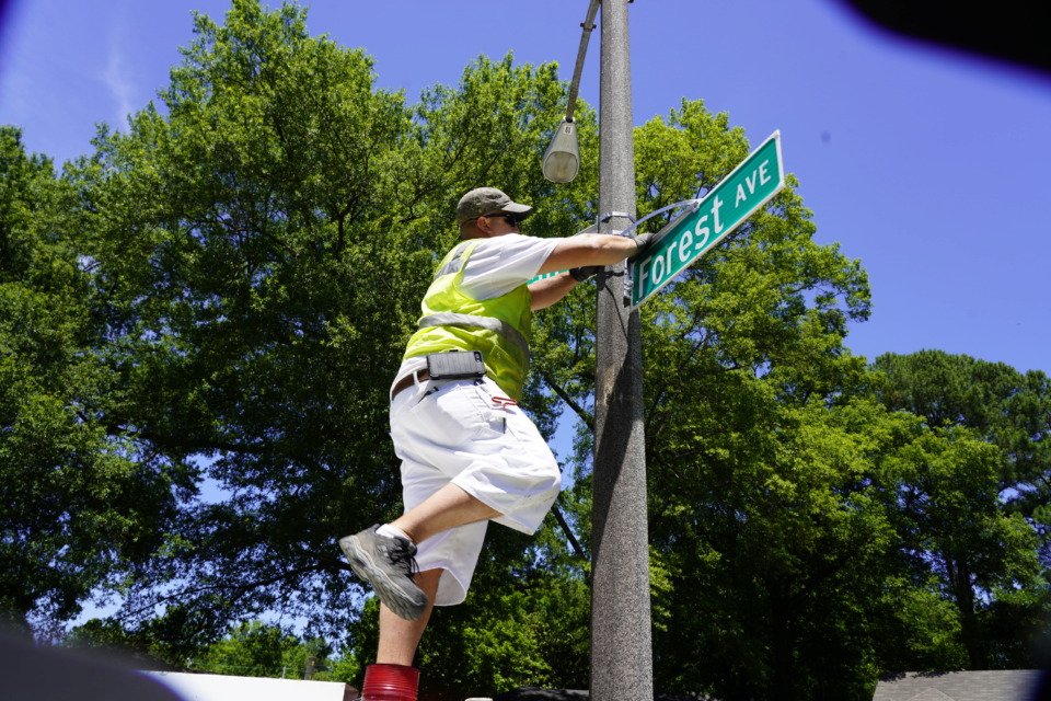 """<strong>City of Memphis painter apprentice Alan Fogler attaches the new """"Forest Ave"""" sign at Forest and Freeman.</strong> (Tom Bailey/The Daily Memphian)&nbsp;"""