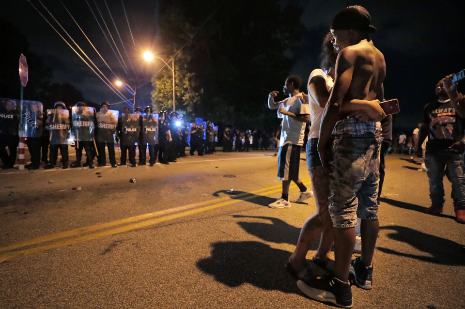 <strong>A man identified as Sonny Webber (right), father of Brandon Webber, who reportedly was shot by U.S. Marshals earlier in the evening, joins a standoff as protesters take to the streets of Frayser to protest the shooting death of Webber. Dozens of protesters clashed with police, throwing stones and tree limbs until police forces broke up the angry crowd with tear gas.</strong>(Jim Weber/Daily Memphian)