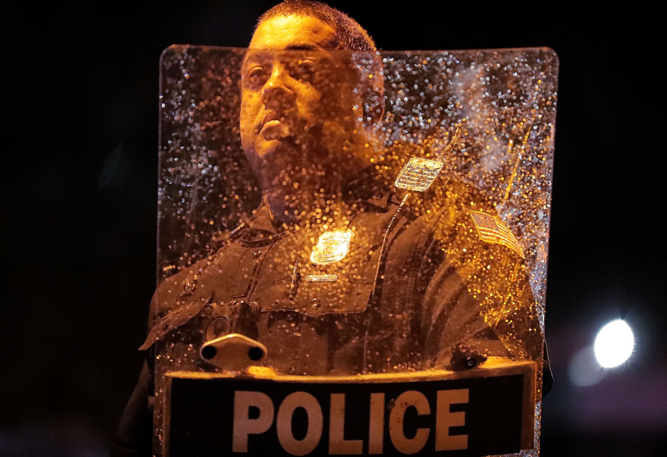 "<strong>Rain and scratches cloud up an officer's riot shield after protesters took to the streets of Frayser in anger over the shooting a youth by U.S. Marshals earlier Wednesday.&nbsp;</strong><span class=""s1""><b>Dozens of protesters clashed with police, throwing stones and tree limbs until police forces broke up the angry crowd with tear gas.</b> (Jim Weber/Daily Memphian)</span>"