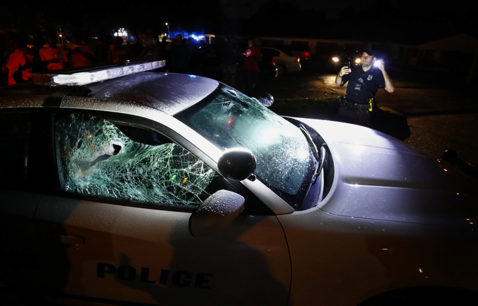 <strong>A Memphis police officer looks over a damaged squad car after protesters took to the streets of Frayser in anger over the shooting of a youth U.S. Marshals earlier Wednesday. Dozens of protesters clashed with police, throwing stones and tree limbs until police forces broke up the angry crowd with tear gas.</strong> (Mark Weber/Daily Memphian)