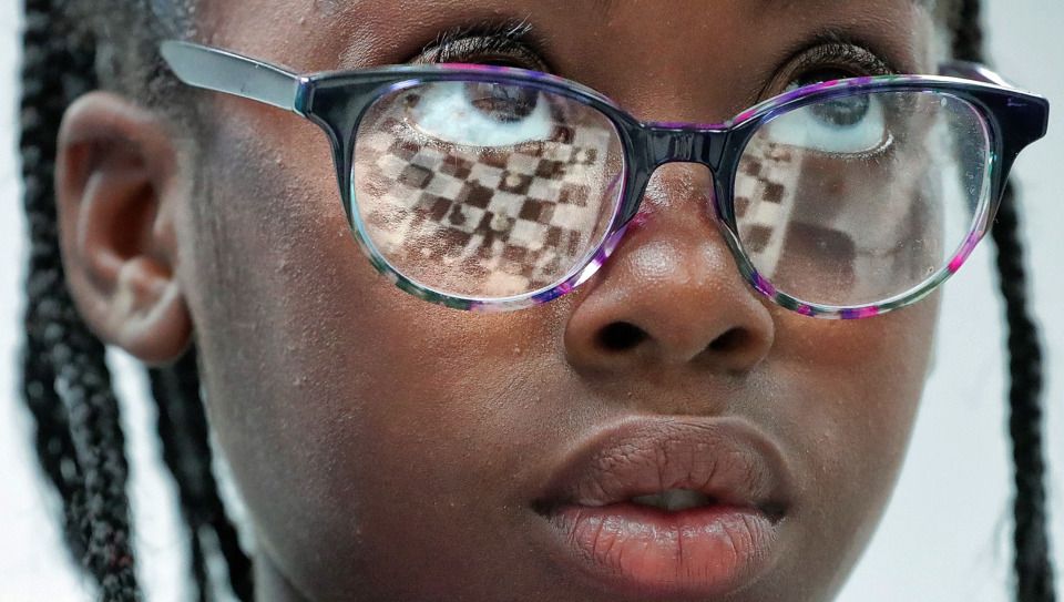 <strong>With the board reflected in her glasses, Kennedi Waller, 10, puzzles through a game against Kaitlyn Cutchin, 12, during the 18th annual Mid-South Chess Camp on the Memphis University School campus this week. More than 120 kids ages 4-16 learn chess from big-name grandmasters, masters and experts.</strong> (Jim Weber/Daily Memphian)