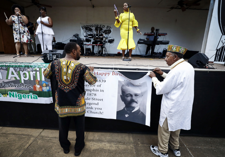 <strong>David L. Acey (right) and his son David L. Acey II hang a banner of Robert R. Church Sr. as Toni Greene (top right) performs during a birthday celebration for Church Tuesday, June 18, 2019. Church, the son of a slave, became one of the first black millionaires in the United States.</strong> (Mark Weber/Daily Memphian)