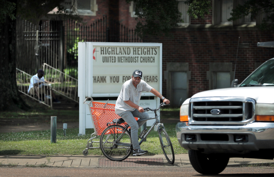 <strong>A cyclist waits for traffic to clear at the corner of Highland and Summer in front of the Highland Heights United Methodist Church, which recently closed after 106 years. The Memphis United Methodist Conference, which owns the property, is hoping that the church building's corner location will be an asset while trying to sell.</strong> (Jim Weber/Daily Memphian)