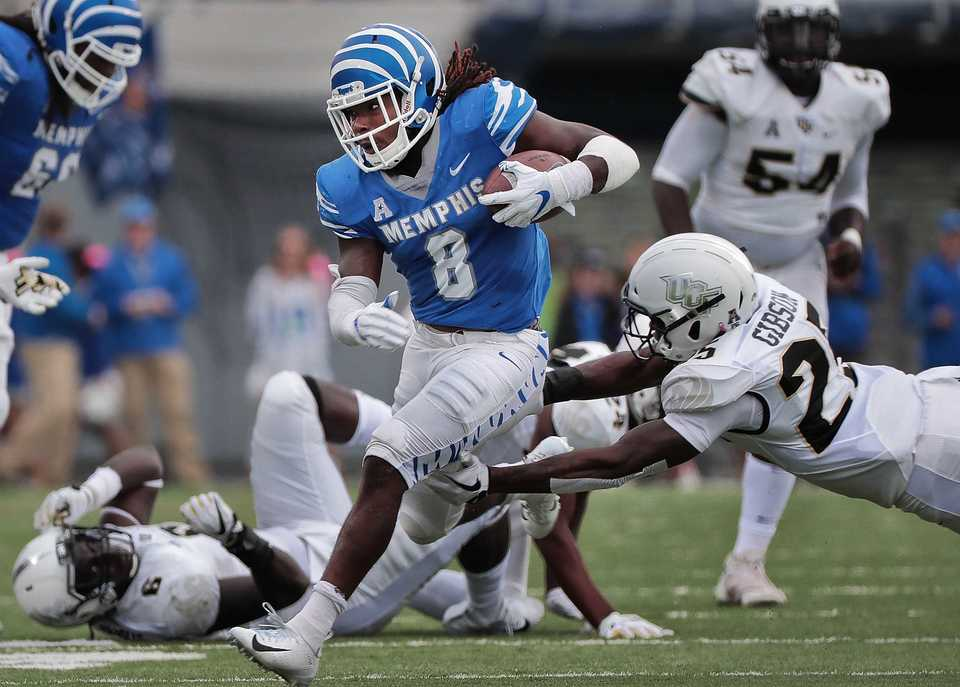 <strong>University of Memphis running back Darrell Henderson (8) breaks a tackle on a run during the Tigers disappointing 31-30 loss to UCF at the Liberty Bowl Memorial Stadium on Saturday, Oct. 13, 2018.</strong> (Jim Weber/Daily Memphian)