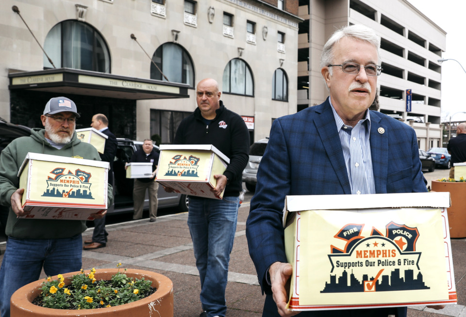 <strong>Danny Todd (right), district vice president of the International Association of Fire Fighters, brings boxes of signed referendum petitions to City Hall alongside Allen Adams (center) and Terry Gilbert (left) on Jan. 14, 2019. The police and fire unions are pushing for a half-cent city sales tax hike to restore health care and retirement benefits cut in 2014. </strong>(Houston Cofield/Daily Memphian file)