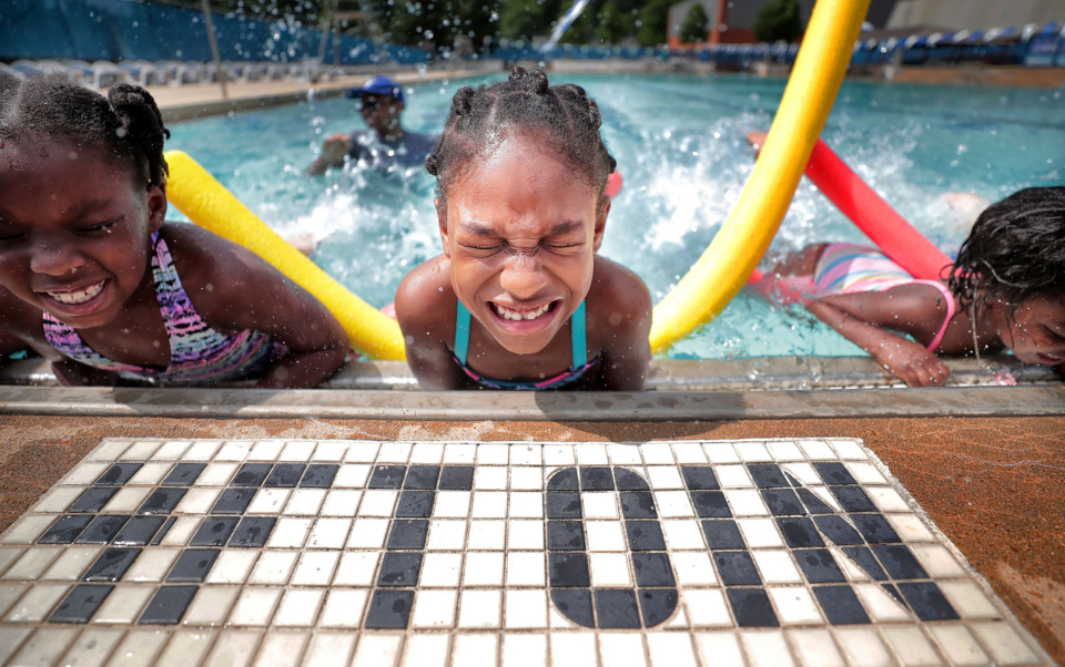 <strong>Cerina Verner (from left), London Tate and LeNayah Lee kick with vigor under the direction of swimming instructor Shepard Saulsberry during The World's Largest Swimming Lesson at the University of Memphis recreation center on Thursday, June 20, 2019. </strong>(Jim Weber/Daily Memphian)