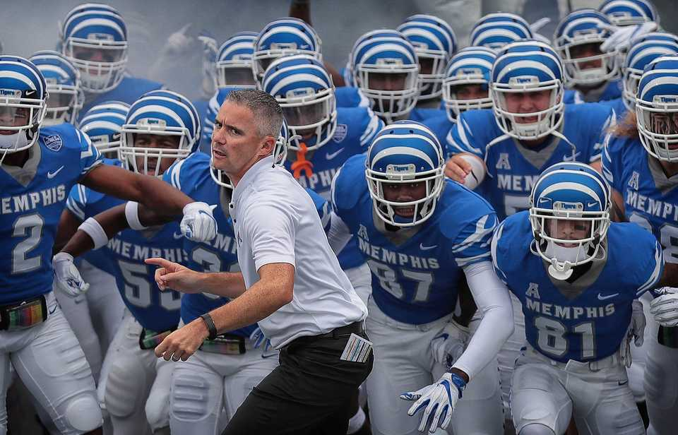 <strong>University of Memphis coach Mike Norvell (center) leads his team onto the field against UCF at the Liberty Bowl Memorial Stadium on Oct. 13, 2018.</strong> (Jim Weber/Daily Memphian)