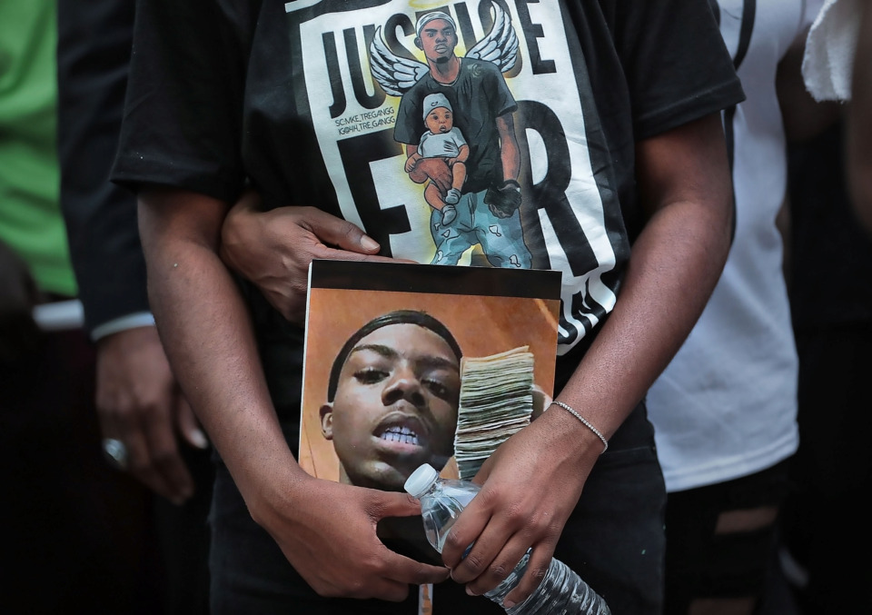 <strong>A family member of 20-year-old Brandon Webber, who was shot by U.S. Marshals Wednesday, June 12, in Frayser, carries a photo of Webber during a vigil on Friday, June 14.&nbsp;Webber was wanted for aggravated assault and robbery after allegedly shooting a man and taking his car. Webber was also, at&nbsp;different points in his life, a college student, social justice leader, honor student and doting father.</strong>&nbsp;(Jim Weber/Daily Memphian)