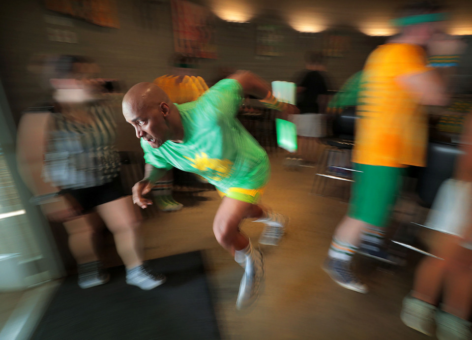 <strong>Baton in hand, Phillip Simms dashes out of the bar at Carolina Watershed after chugging a beer while competing in a bar relay race Saturday during the Downtown Olympics at Loflin Yard.</strong> (Jim Weber/Daily Memphian)