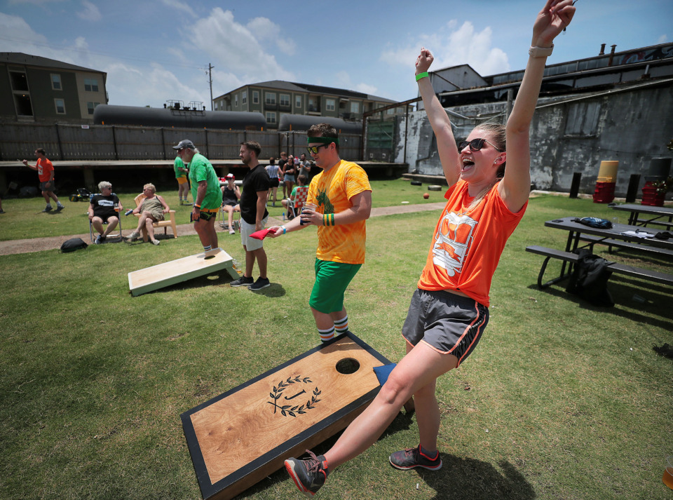 <strong>Mary Kate Henderson with the Front Street Four team celebrates a score while playing cornhole during the Downtown Olympics at Loflin Yard.</strong>&nbsp;(Jim Weber/Daily Memphian)