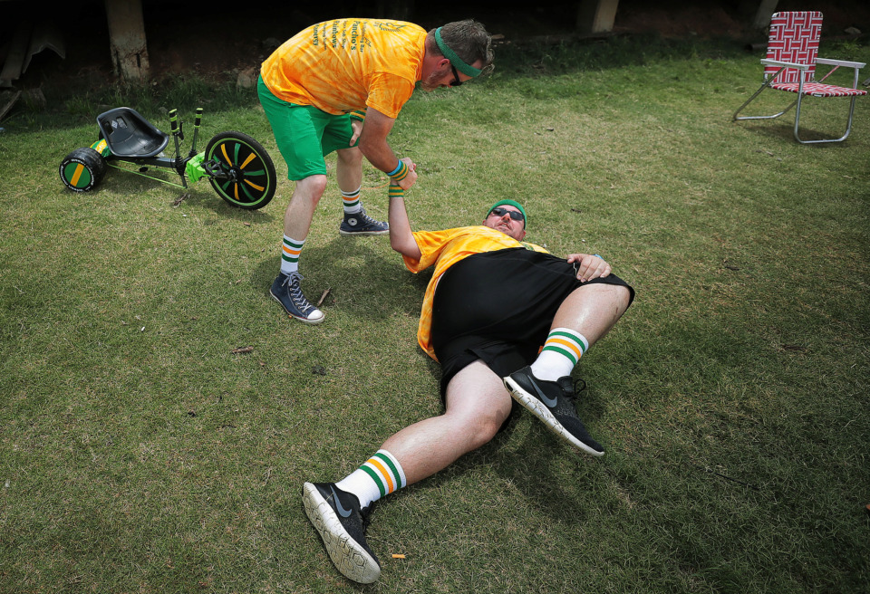 <strong>Brady Hummel with the Yellow Unicorns stretches between beer pong games Saturday. Other competitions included tricycle racing and cornhole.</strong>&nbsp;(Jim Weber/Daily Memphian)