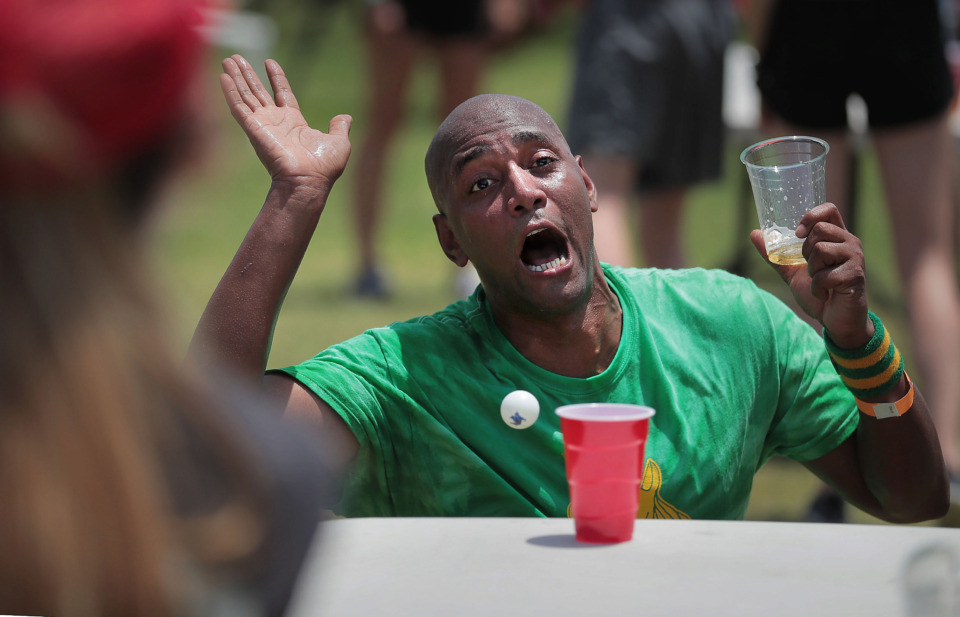 <strong>Phillip Simms with the Green Unicorns tries to distract the competiton in beer pong during the Downtown Olympics. Local teams also vied in cornhole and tricycle racing to benefit the Urban Bicycle Food Ministry.</strong> (Jim Weber/Daily Memphian)
