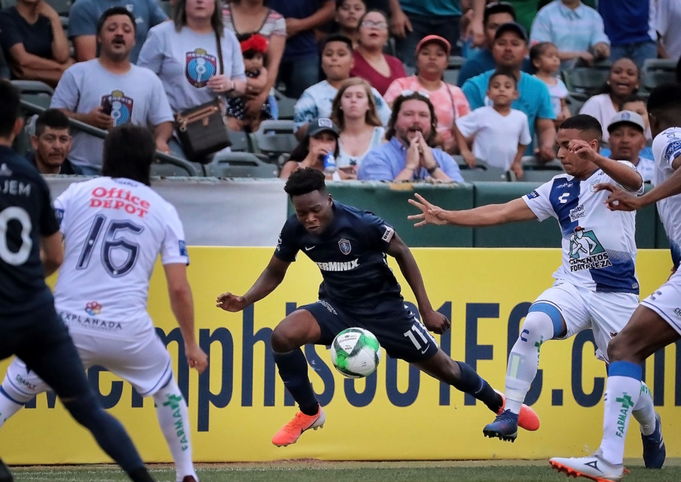 <strong>Memphis forward Lagos Kunga is tripped up by a Pachuca defender during 901 FC's 6-1 loss to the squad from Mexico.</strong> (Jim Weber/Daily Memphian)