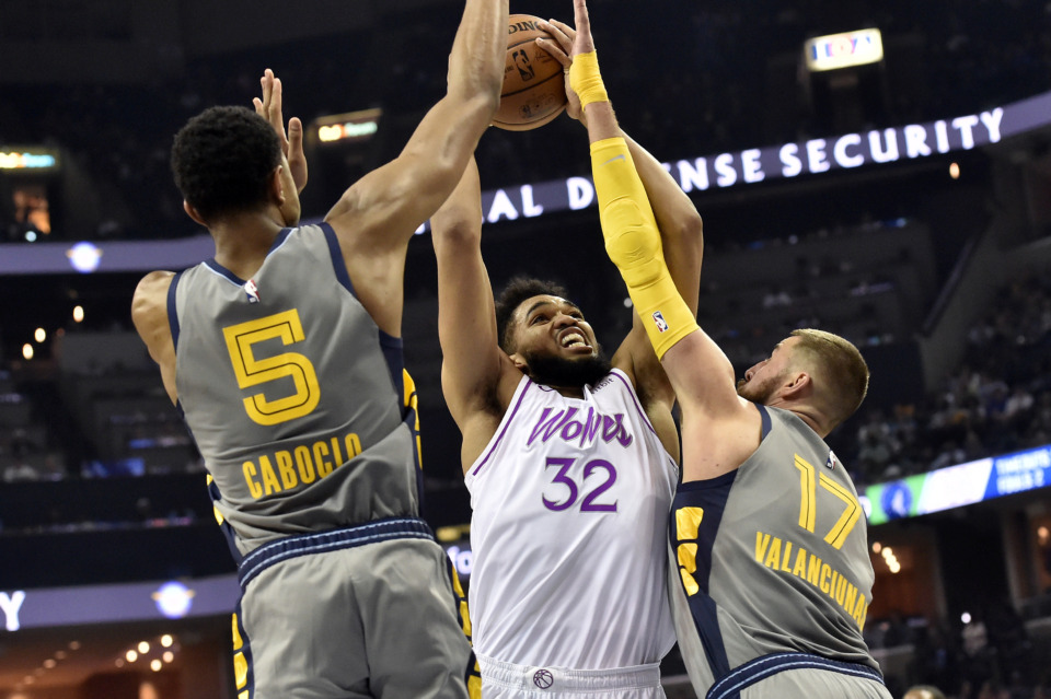 <span><strong>Minnesota Timberwolves center Karl-Anthony Towns (32) shoots against Memphis Grizzlies center Jonas Valanciunas (17) and forward Bruno Caboclo (5) in the second half of an NBA basketball game Saturday, March 23, 2019, in Memphis, Tenn.</strong> (AP Photo/Brandon Dill)</span>