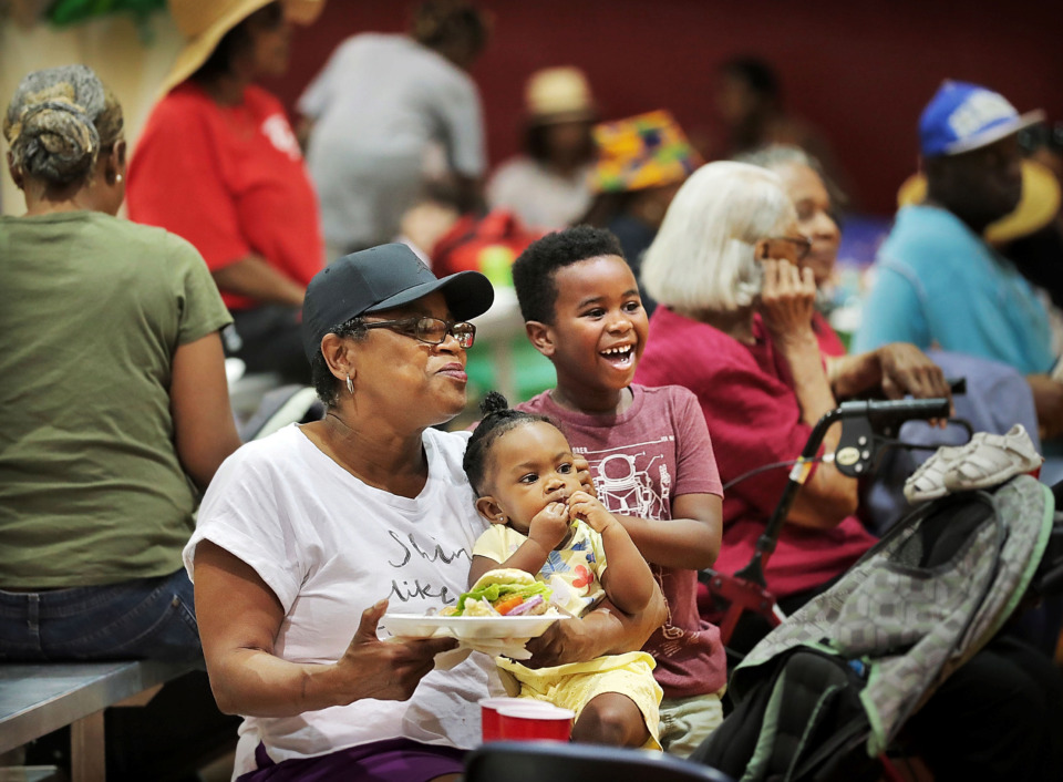 <strong>Jacqueline Jones (left) spends an afternoon watching her grandson Elias James (right) play in the bounce house and eating lunch with 1-year-old Kinslee Adams during a rally on June 29, 2019 at the Bickford Community Center in North Memphis. The rally organized by Friends of the Earth was held to&nbsp; build momentum behind a $250 million, five-year weatherization program in Memphis.</strong> (Jim Weber/Daily Memphian)
