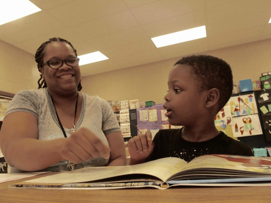 <strong>Teacher Dorian Lloyd helps rising first-grader Nykari McNeal sound out words during a state-funded reading camp at Cornerstone Prep, a charter school in Memphis. It's unclear if the state will continue to fund the popular statewide program next summer.&nbsp;</strong>(Kathryn Palmer/Chalkbeat)